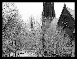 Verschneite Kirche hinter Bäumen